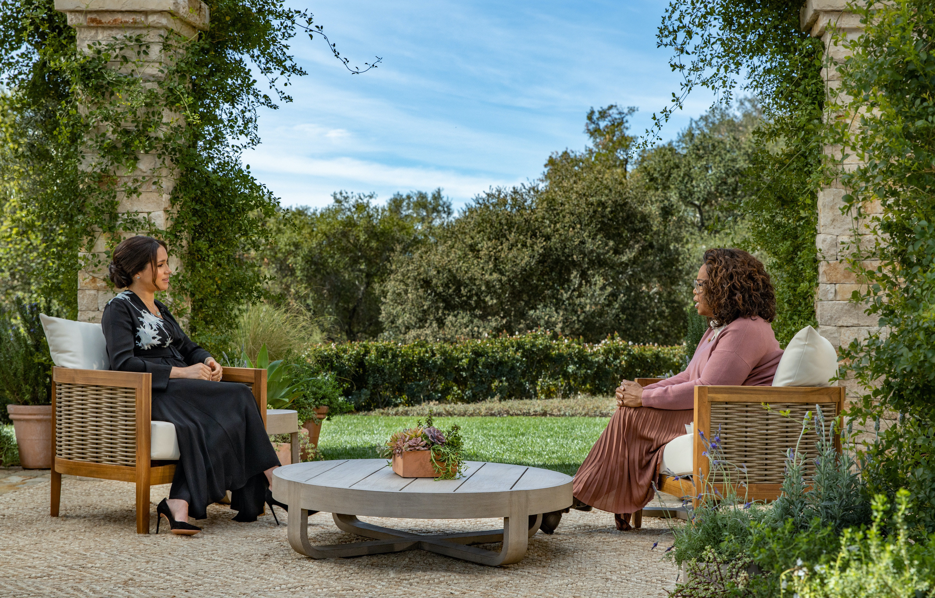 Meghan Markle sits down while being interviewed by Oprah