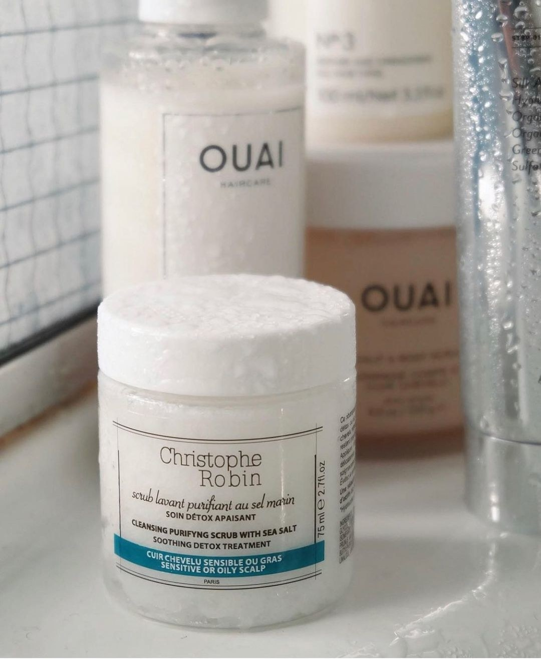 A small container of hair scrub on a counter next to other beauty products