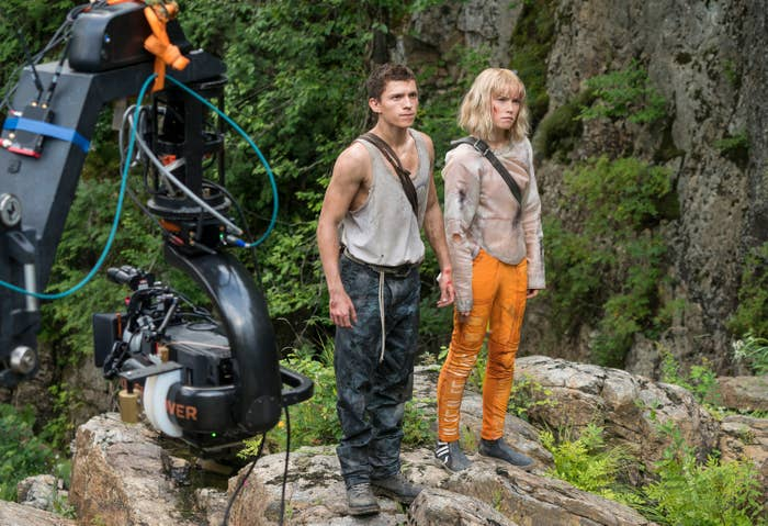 Tom Holland and Daisy Ridley as Todd and Viola stand together on a rock