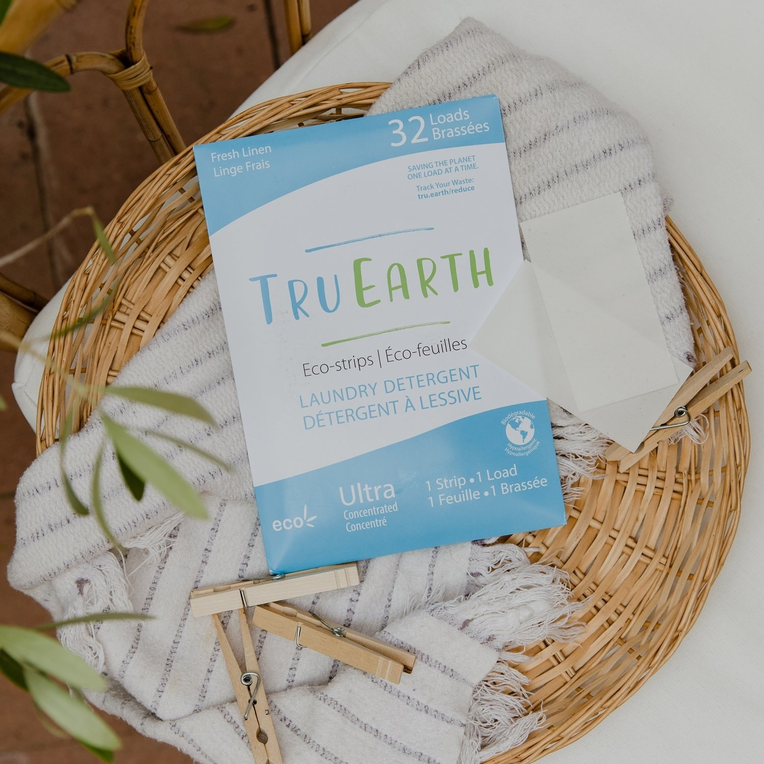 a bag of tru earth eco-strips laundry detergent in a woven basket with a cloth and clothes pins