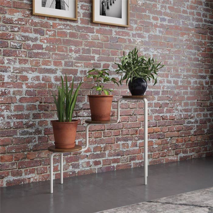 A 3-tier brown and white plant stand
