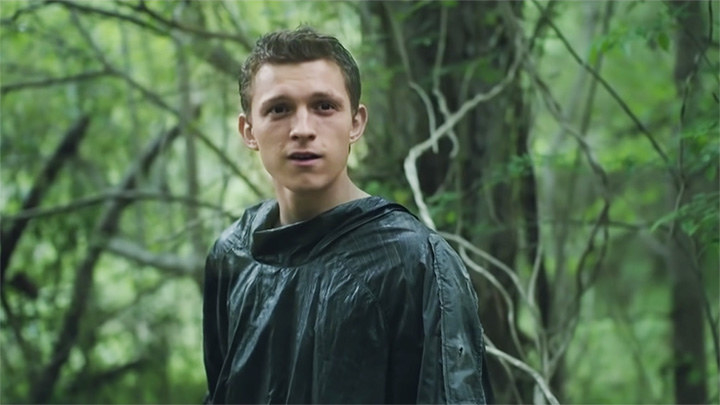 Tom Holland playing todd in the movie chaos walking. he is about to talk while standing in the woods and appears startled.