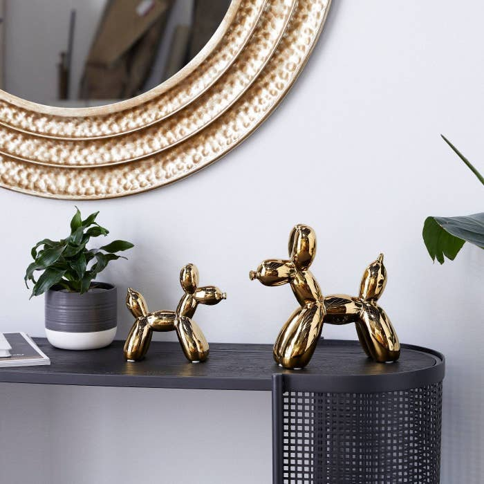 A set of gold balloon dogs on a black table