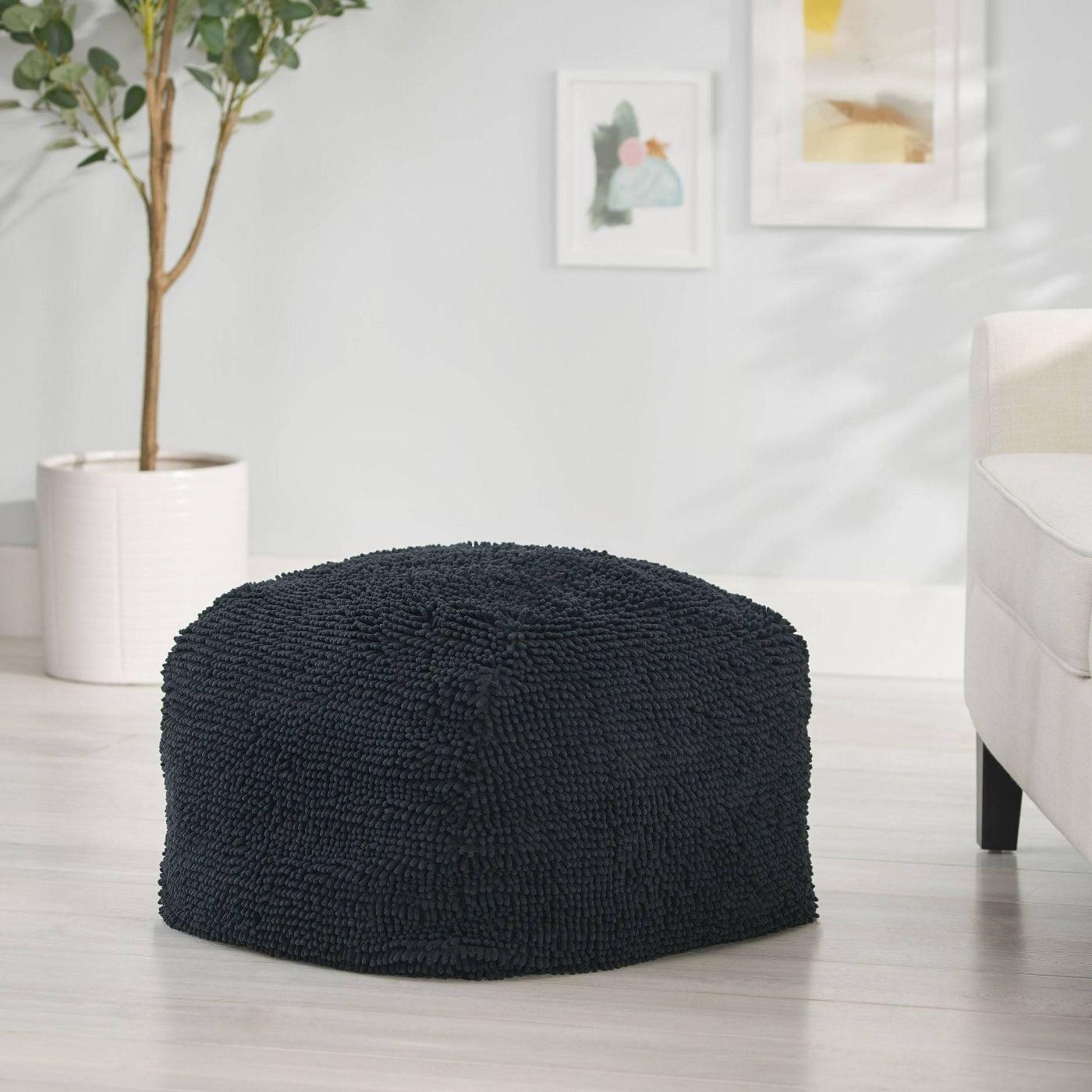 A black fuzzy ottoman in a home