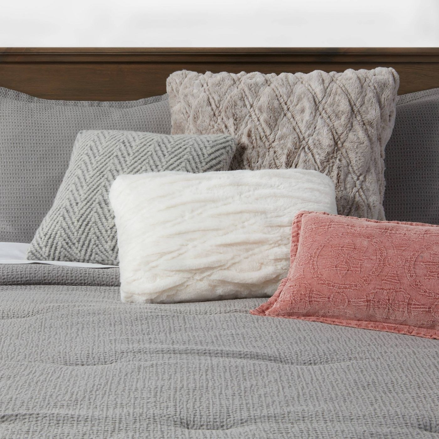 A white pillow with a pink and neutral pillow