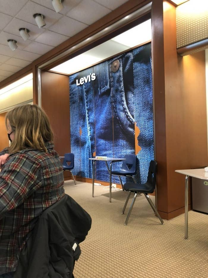 Levi's signage remains up behind school desks, a student in the foreground sits wearing a face mask