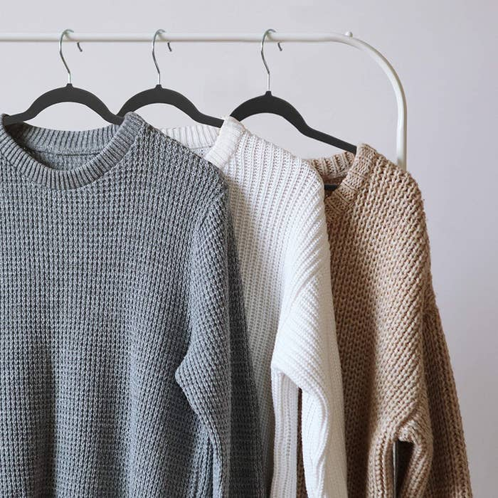 A trio of velvet hangers with sweaters hung on them