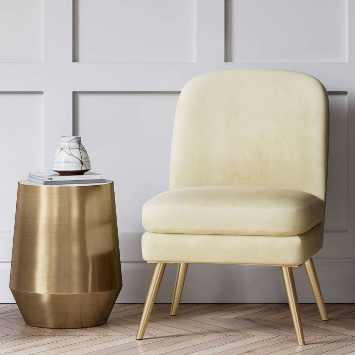 A white slipper-style chair with gold leg