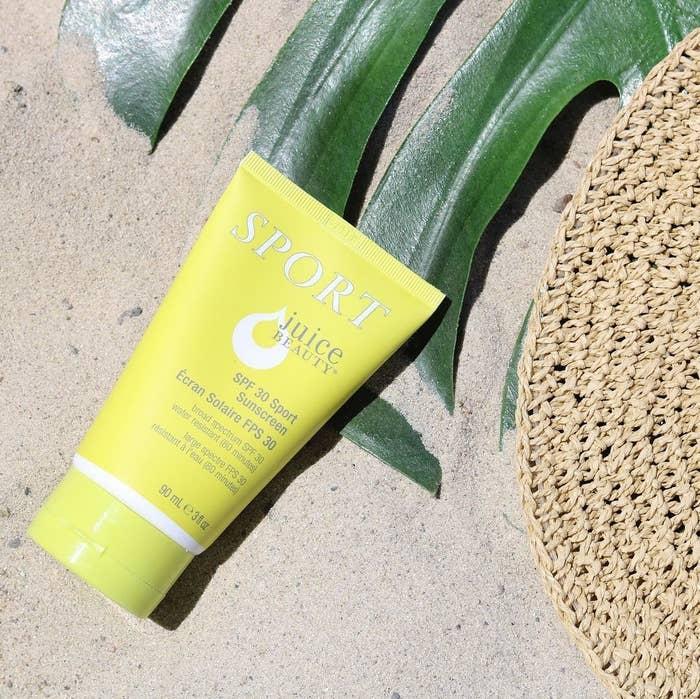 A tube of sunscreen lying on sand