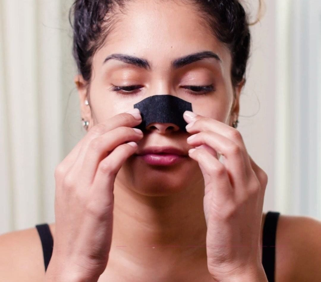 A person removing one of the pore strips from their nose
