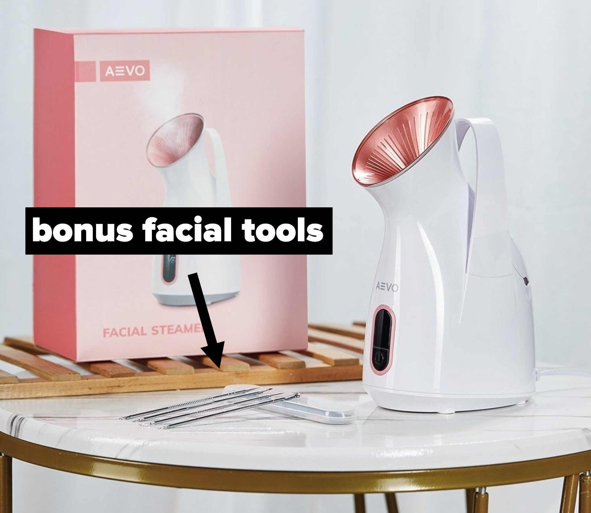 The facial steamer on a low table next to four face tools