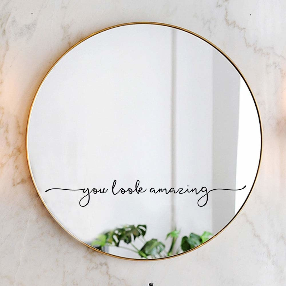 """script decal that says """"you look amazing"""" on a circular gold mirror"""