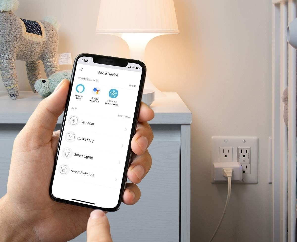 person using their phone to control the smart plug which a lamp is plugged into