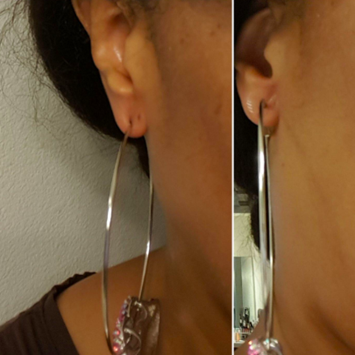 Reviewer with large hoop earring pulling at their earlobe before use and sitting upright and in the center after adding the adjuster