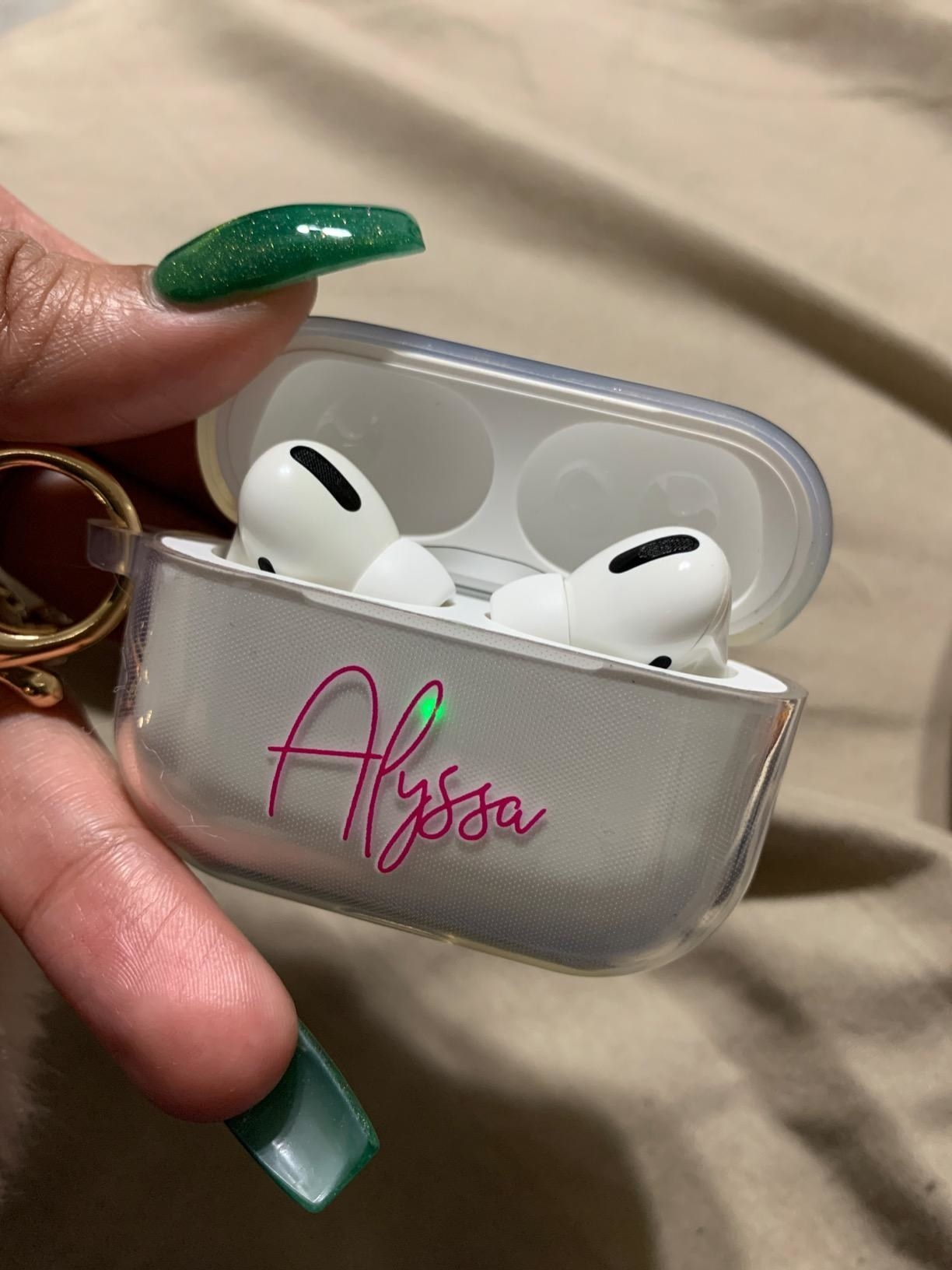 """hands hold silver AirPods case that says """"Alyssa"""" on front in pink letters"""