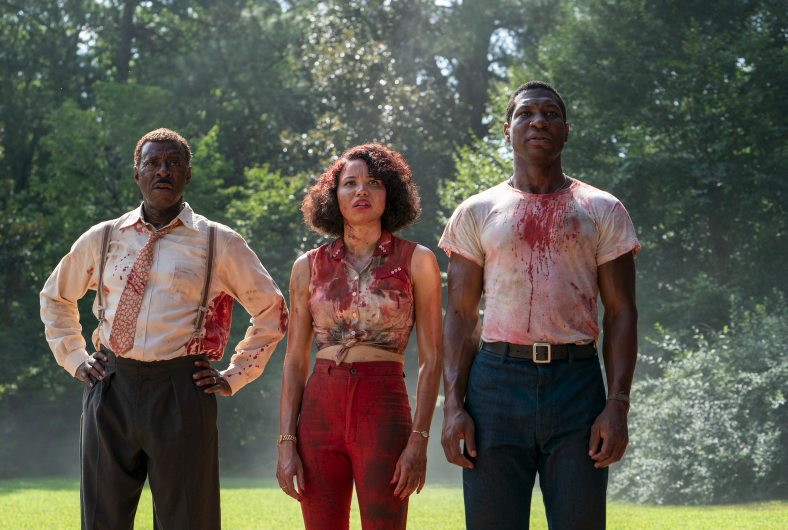 Three people stand side by side, looking in the distance, their outfits covered in blood