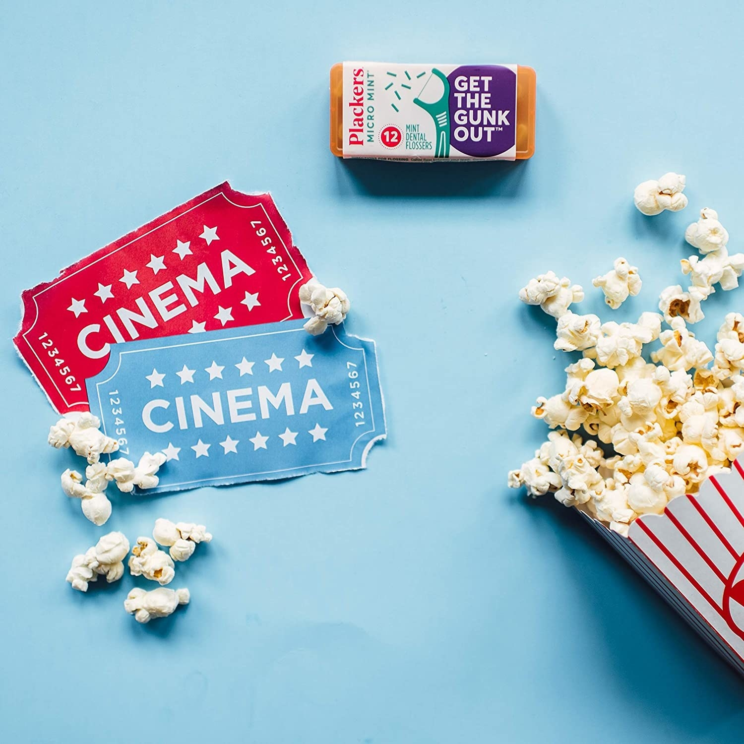Floss pick pack beside movie popcorn and tickets