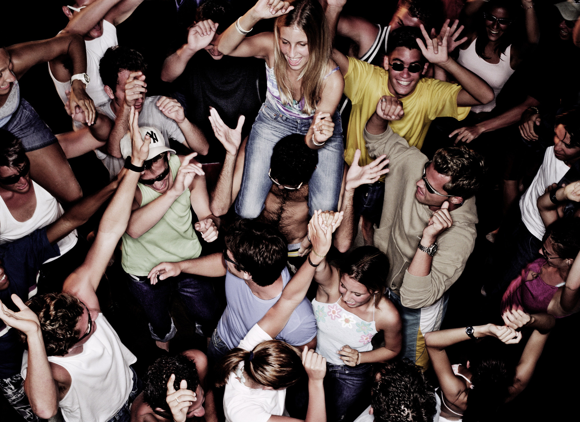 A group of people dancing at a packed party
