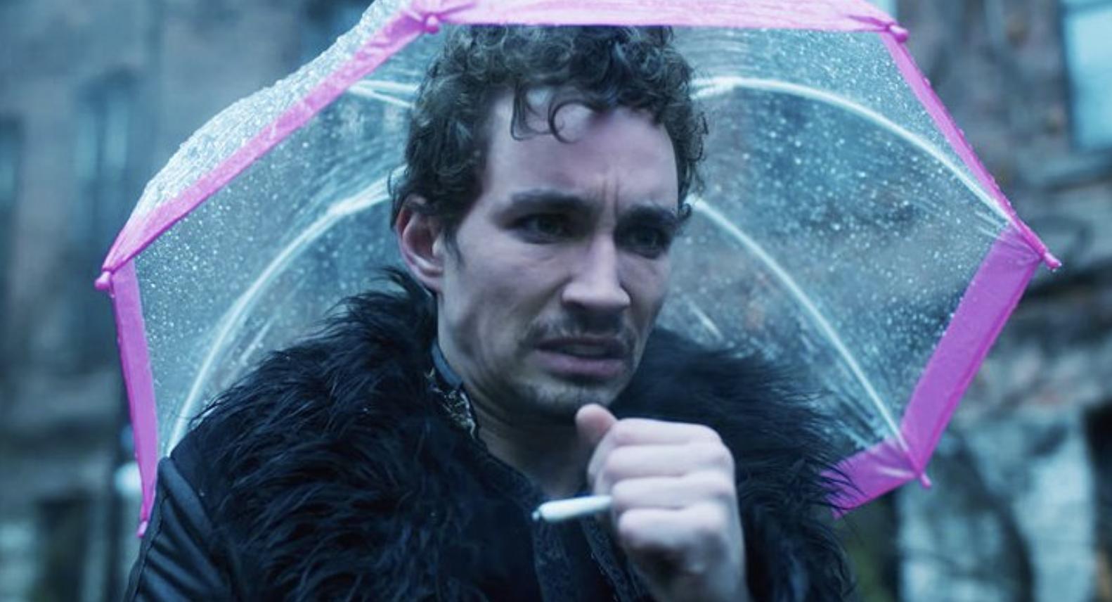 "Robert in ""Umbrella Academy,"" holding a cigarette and pink umbrella"