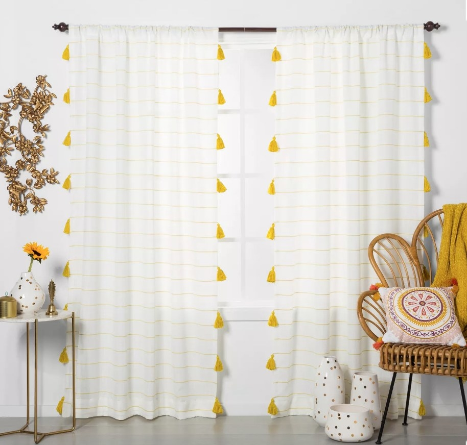 White curtains with yellow pinstripe and yellow tassles