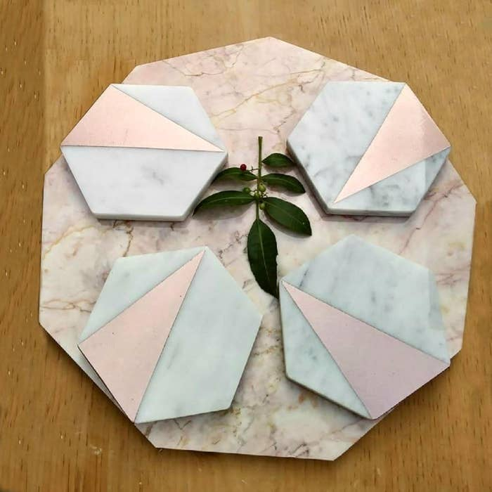 Four rose gold coasters placed on table