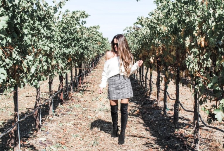 A reviewer wearing the skirt with knee high boots and a white sweater in an orchard
