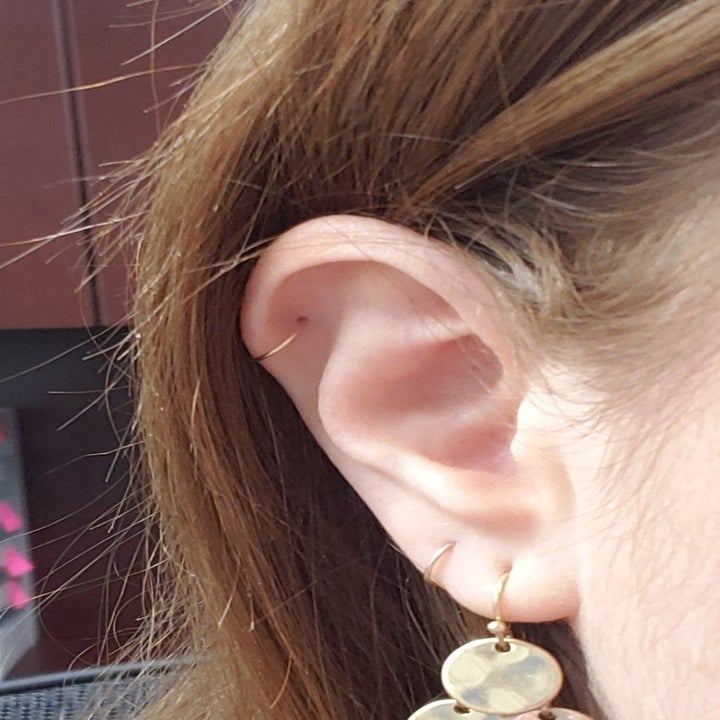 reviewer wears small gold hoop earrings on lobes and cartilage area of ear