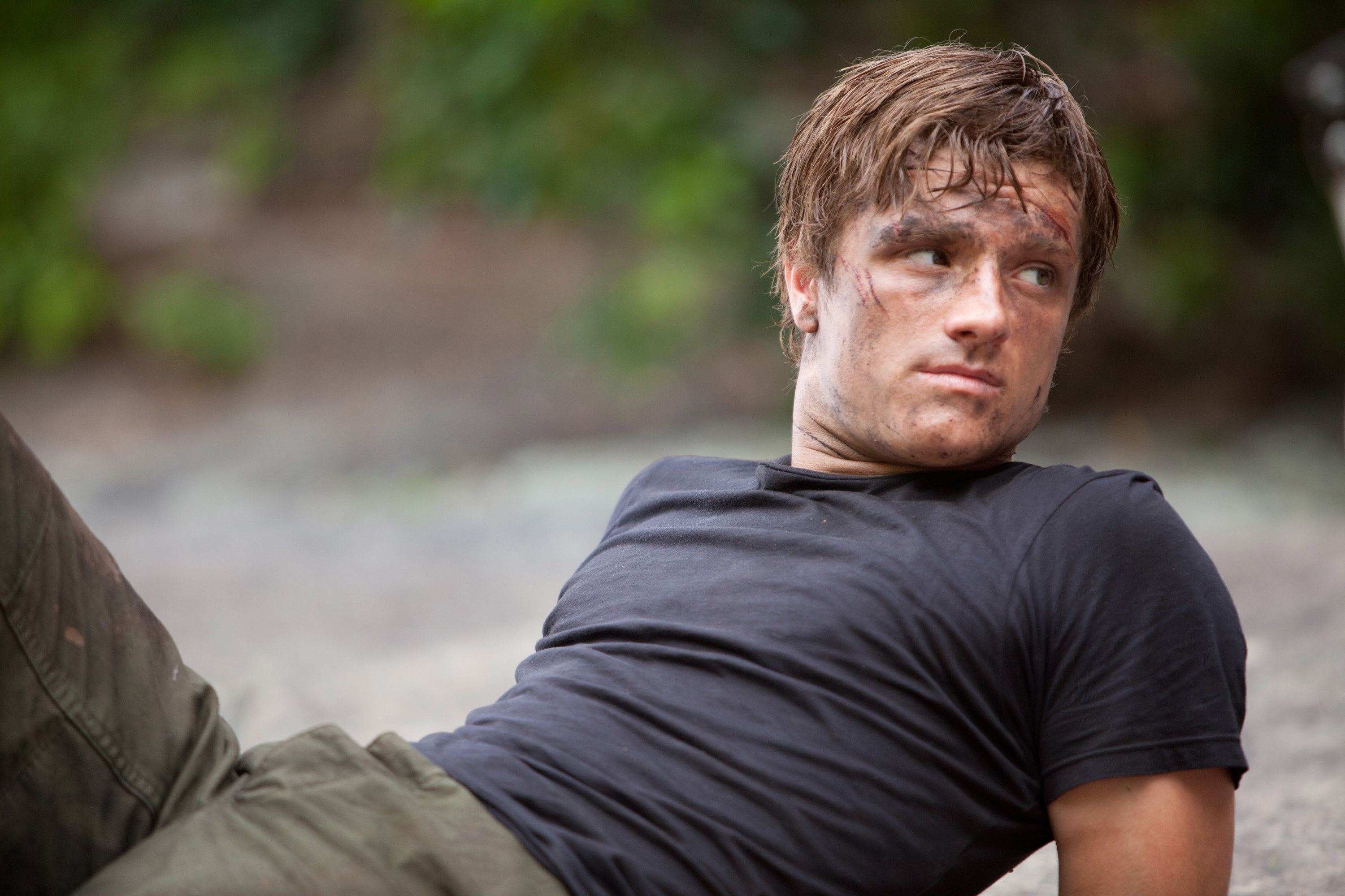 Peeta lying on the ground covered in dirt