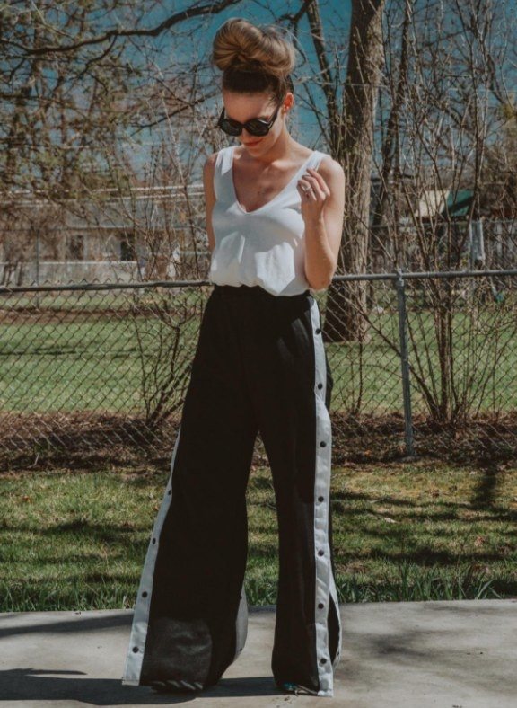 Reviewer wearing the pants in black and white with a white top and sunglasses