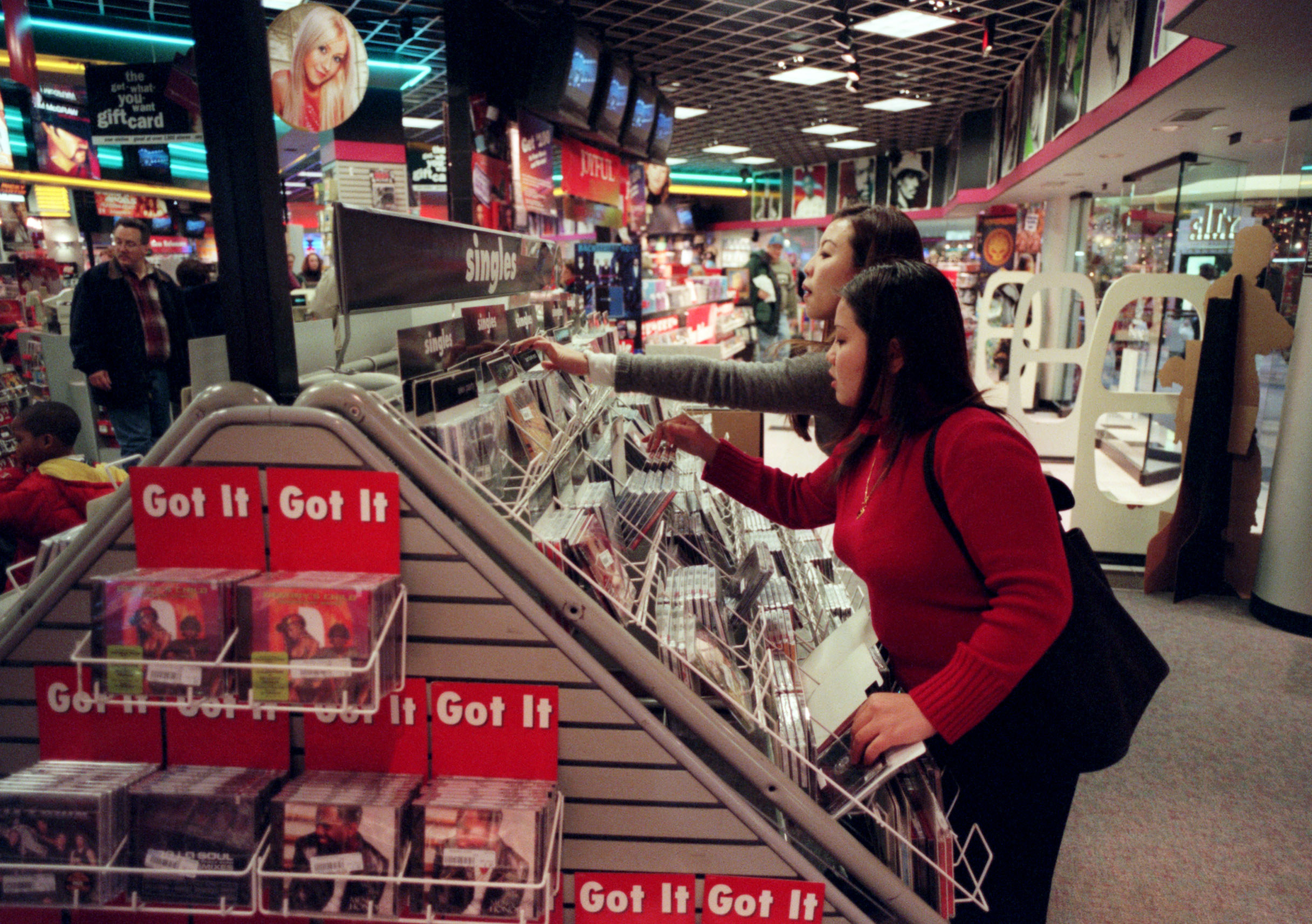 Two woman looking for CDs at Sam Goody's