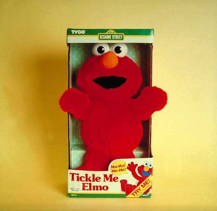 A Tickle Me Elmo doll in its package with a yellow background