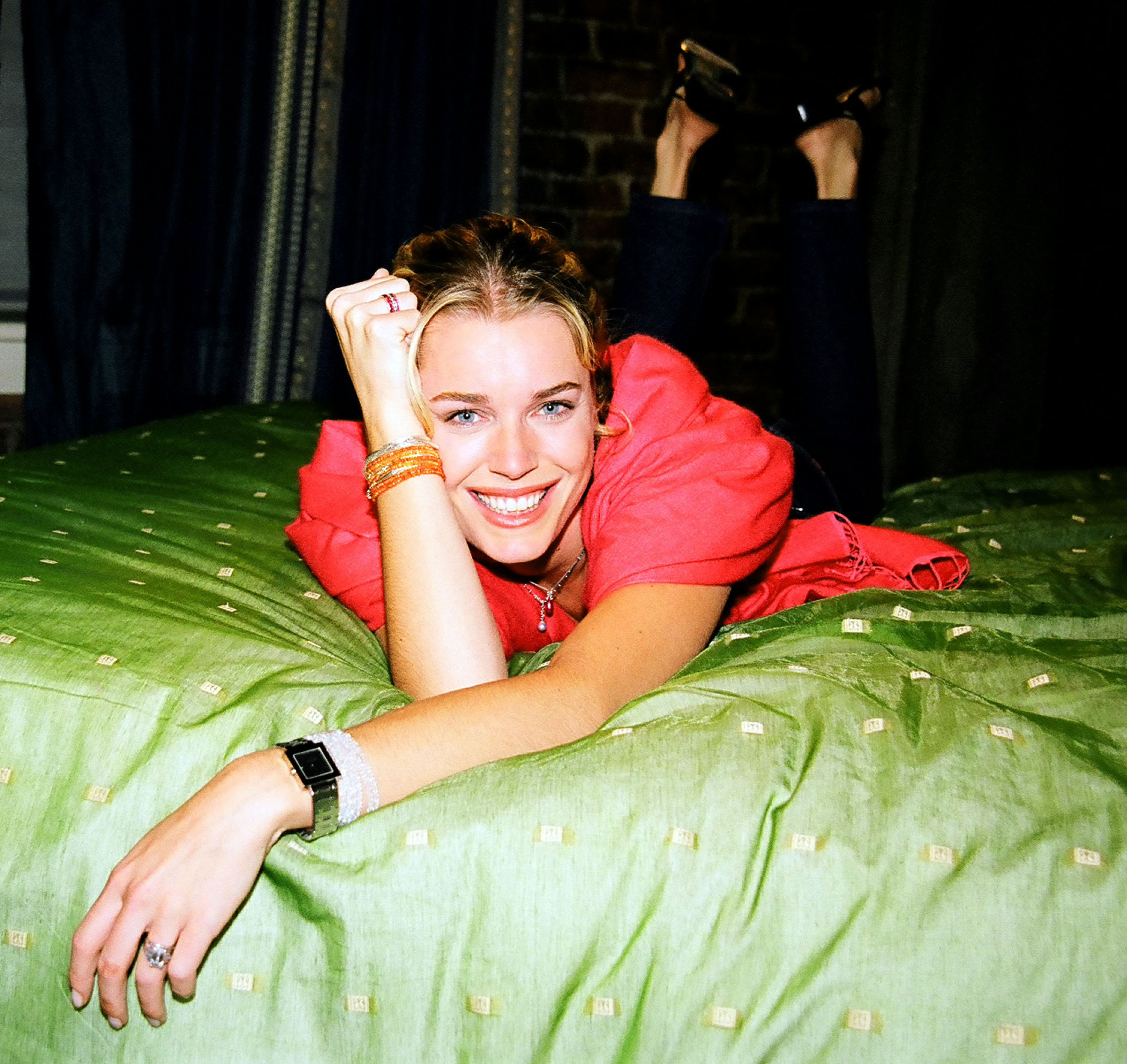 Rebecca Romijn laying on a bed with a green cover