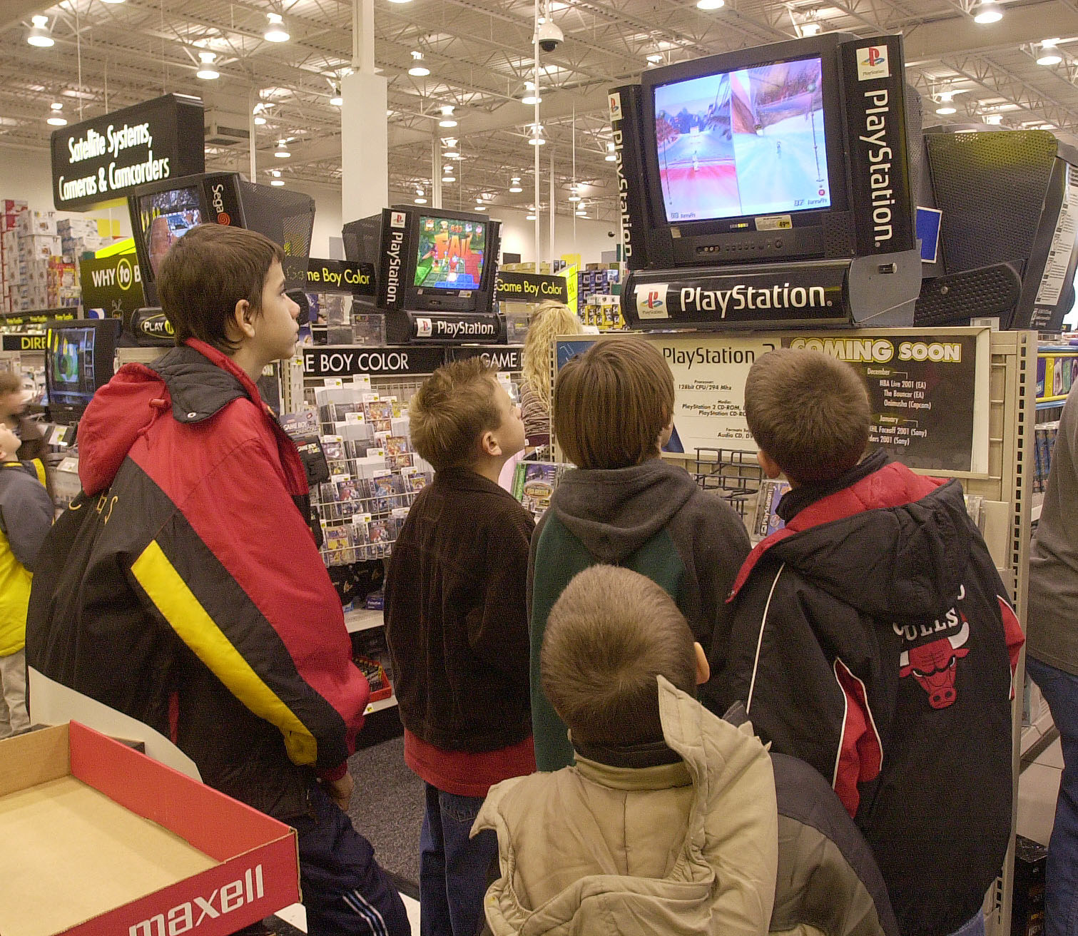 A bunch of kids playing PlayStation in a display at a Best Buy