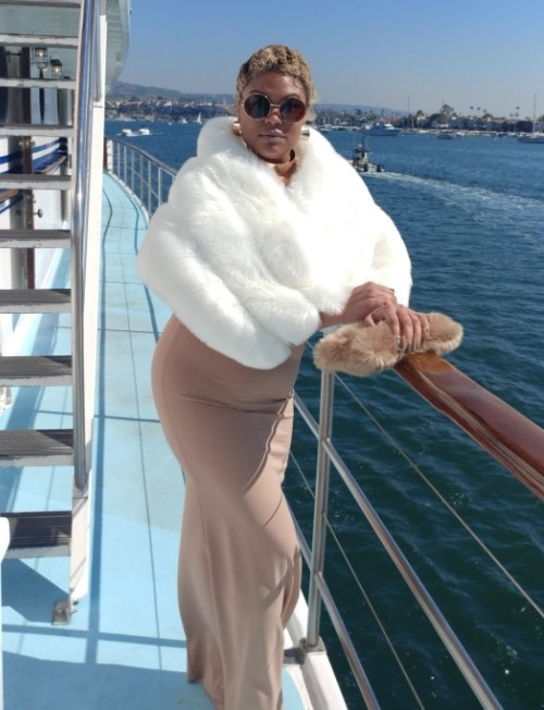 A reviewer wearing the faux fur wrap in white while on a boat