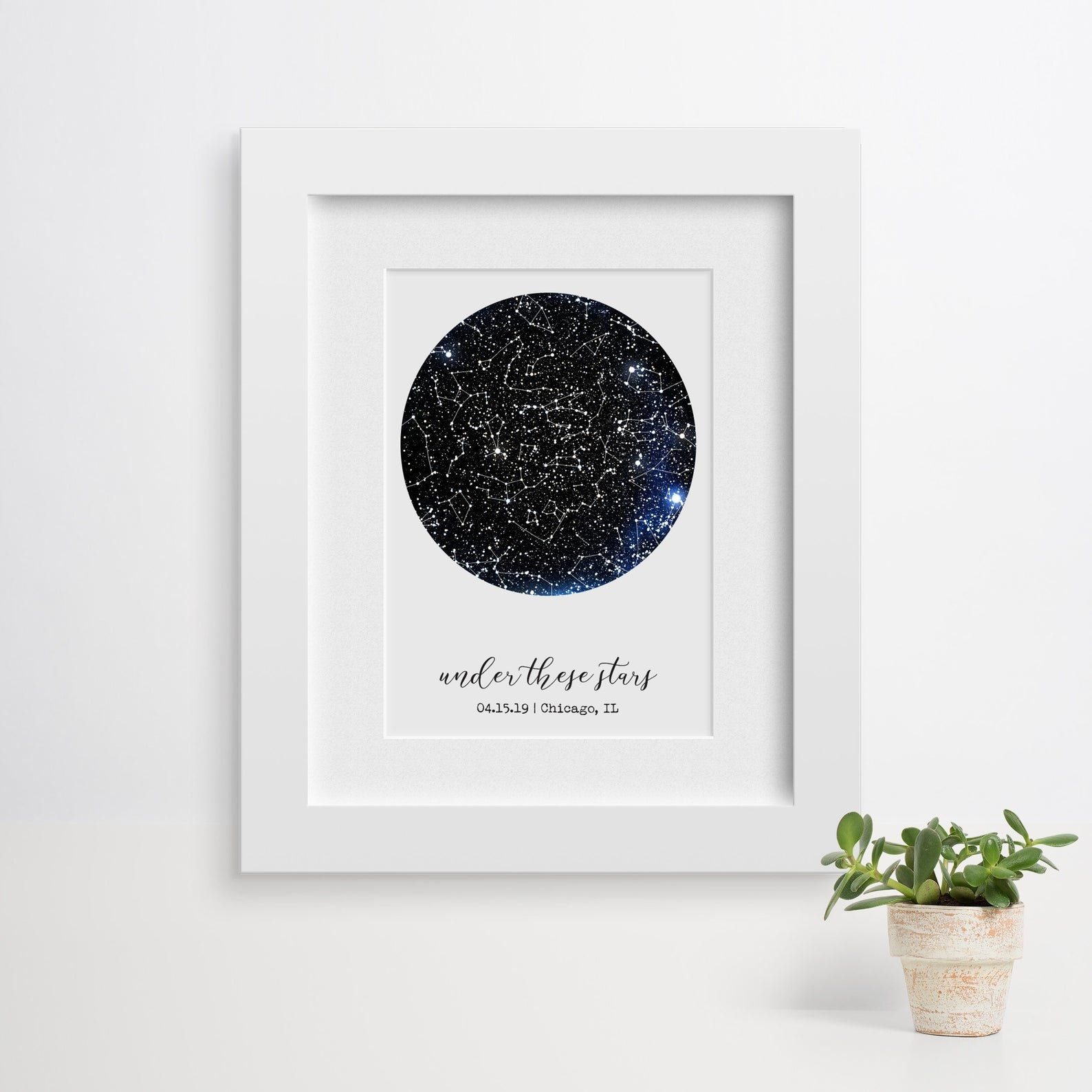Customized constellation print with white mat and white frame hanging on wall