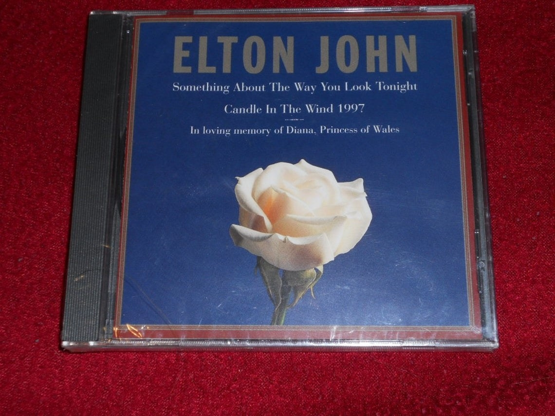 A CD of Candle in the Wind 1997 which features a white rose with a blue background on the cover