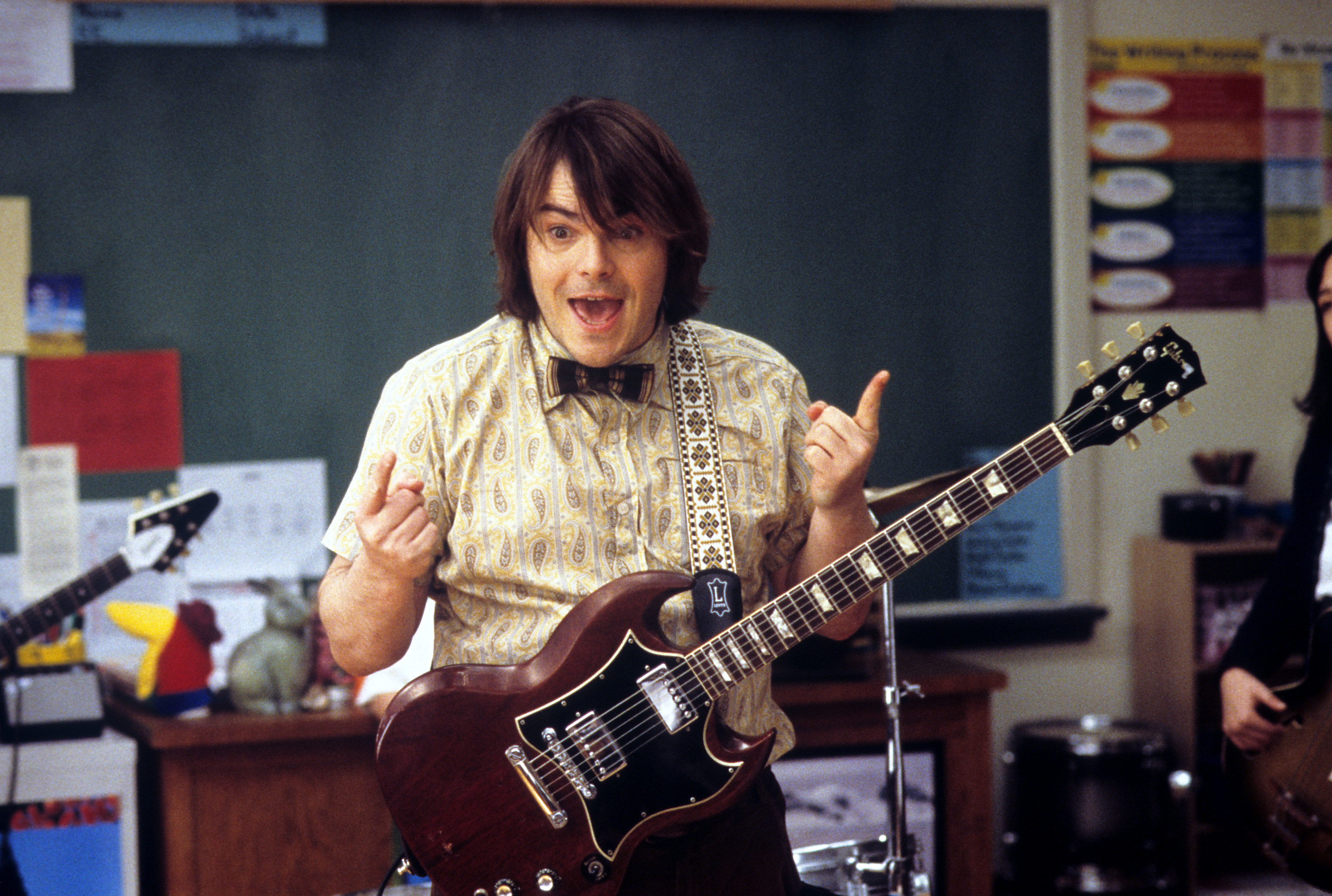 """Jack Black playing a guitar in a classroom in """"School of Rock"""""""