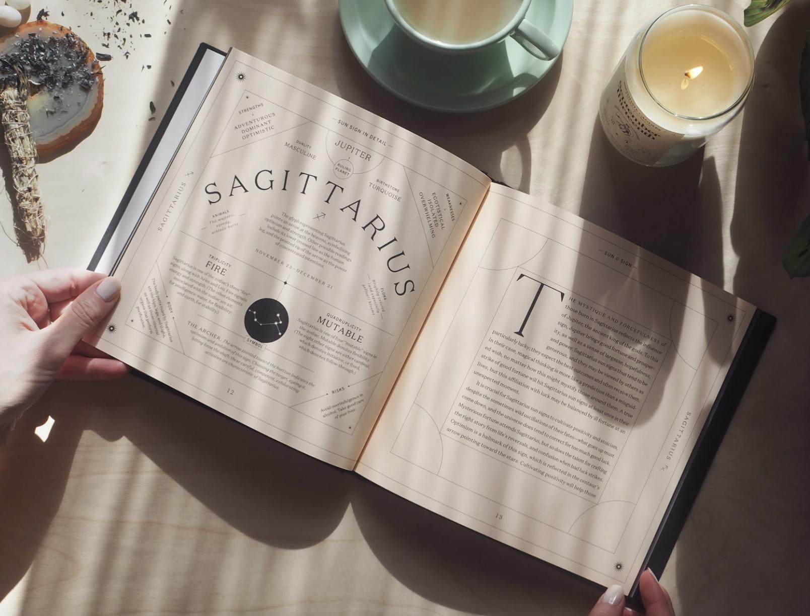 "hands open Birthdate Co. Birthdate Book to a page that says ""Sagittarius"""