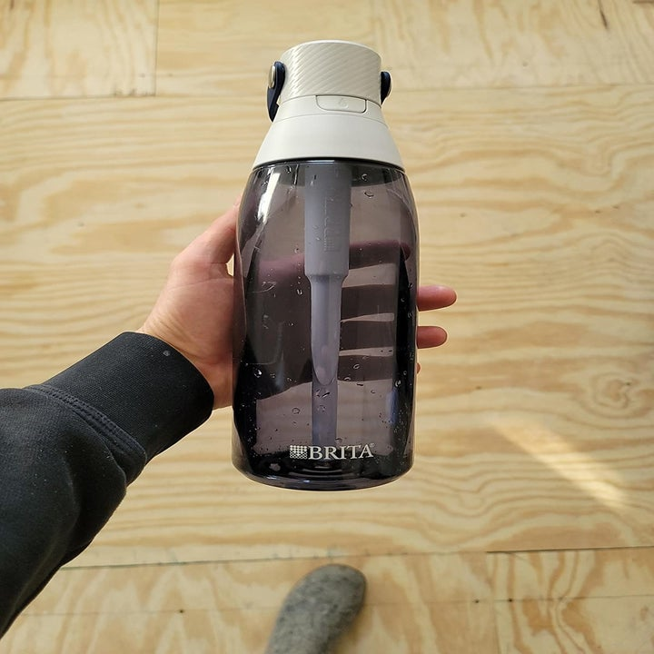 person holding up a black water bottle with a brita filter in it