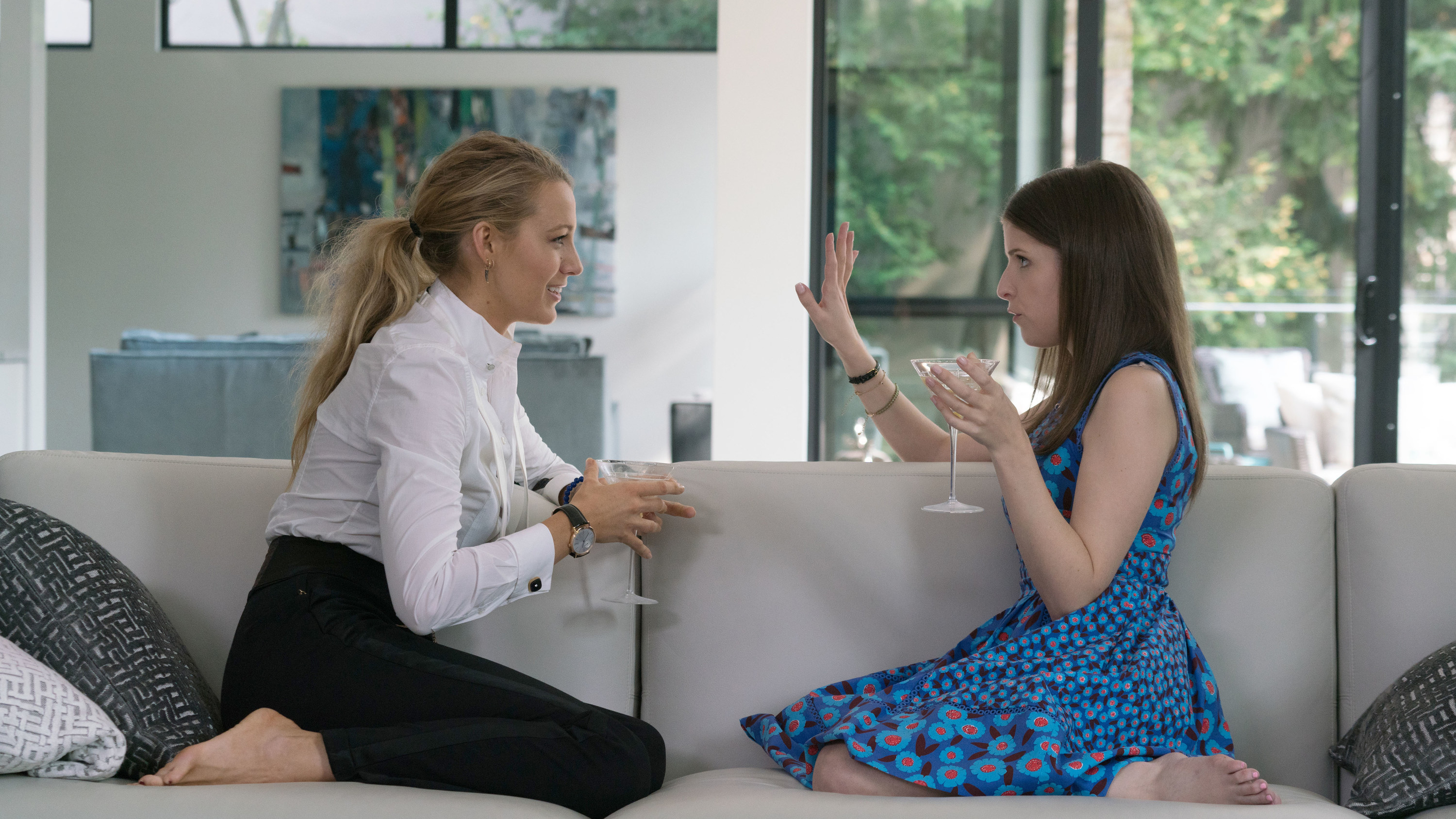 """Blake Lively and Anna Kendrick sitting on a couch and sipping drinks in """"A SImple Favor"""""""