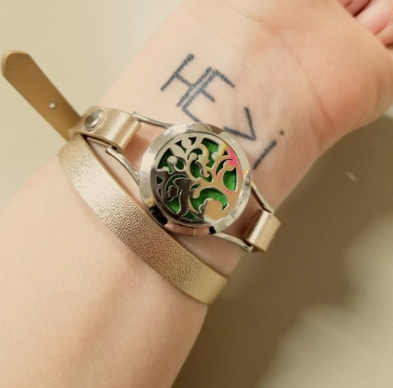 Reviewer wearing the bracelet in green over her tattooed wrist
