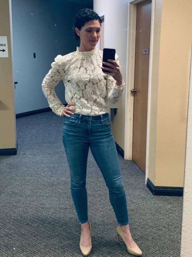 A reviewer wearing the blouse in white with blue jeans