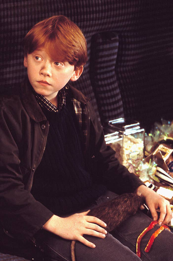 Rupert Grint as Ron Weasley with a rat on his lap in Harry Potter and the Sorcerer's Stone