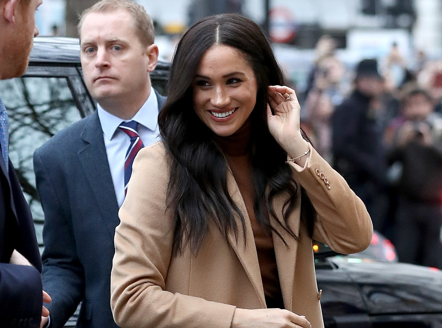 Meghan smiles in a beige wool coat on the way to an event while a crowd stands behind her