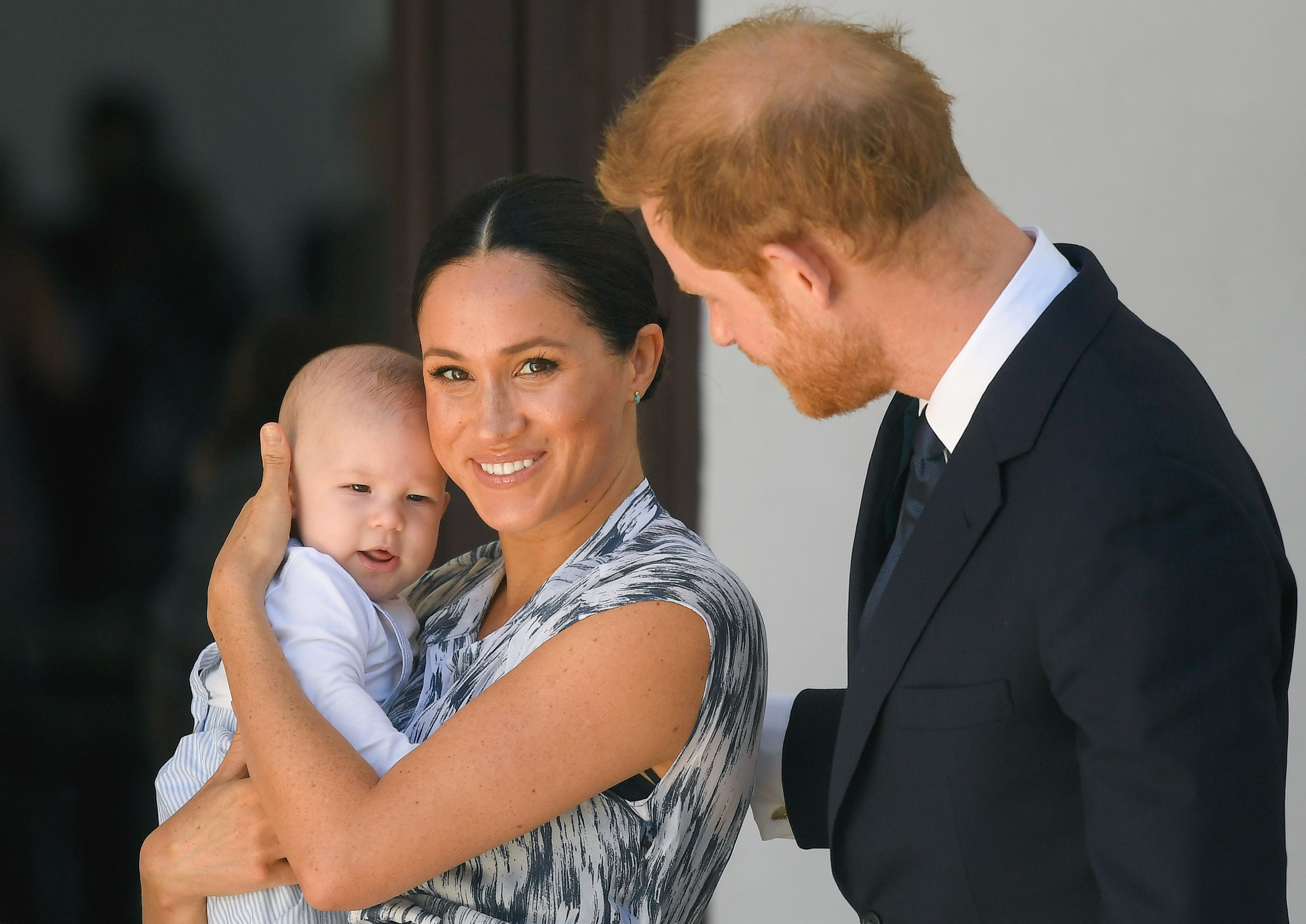 Meghan smiles while holding Archie and Harry puts his arm around her