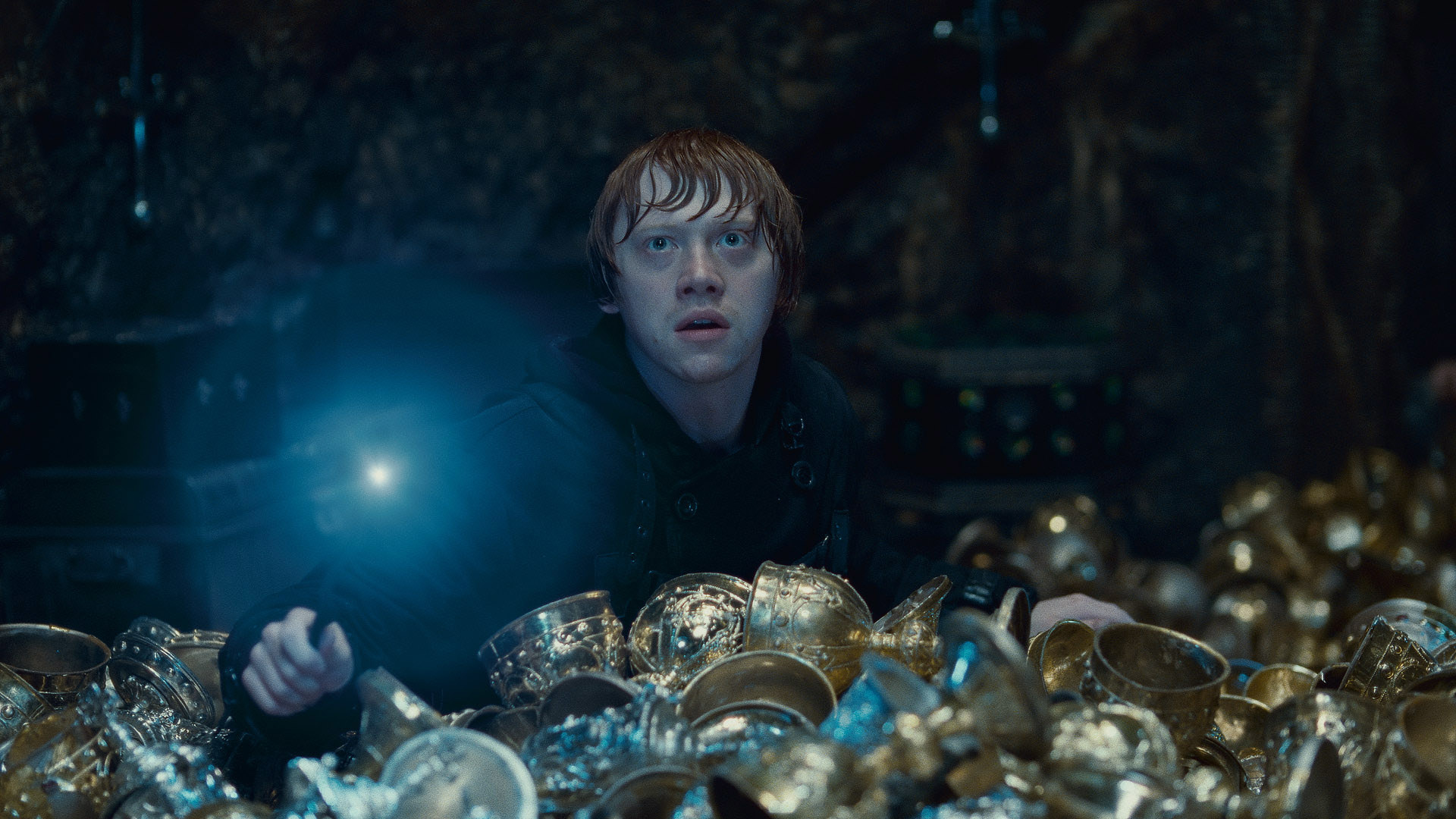 Rupert Grint holds a glowing wand amidst gold cups in Harry Potter and the Deathly Hallows: Part 2