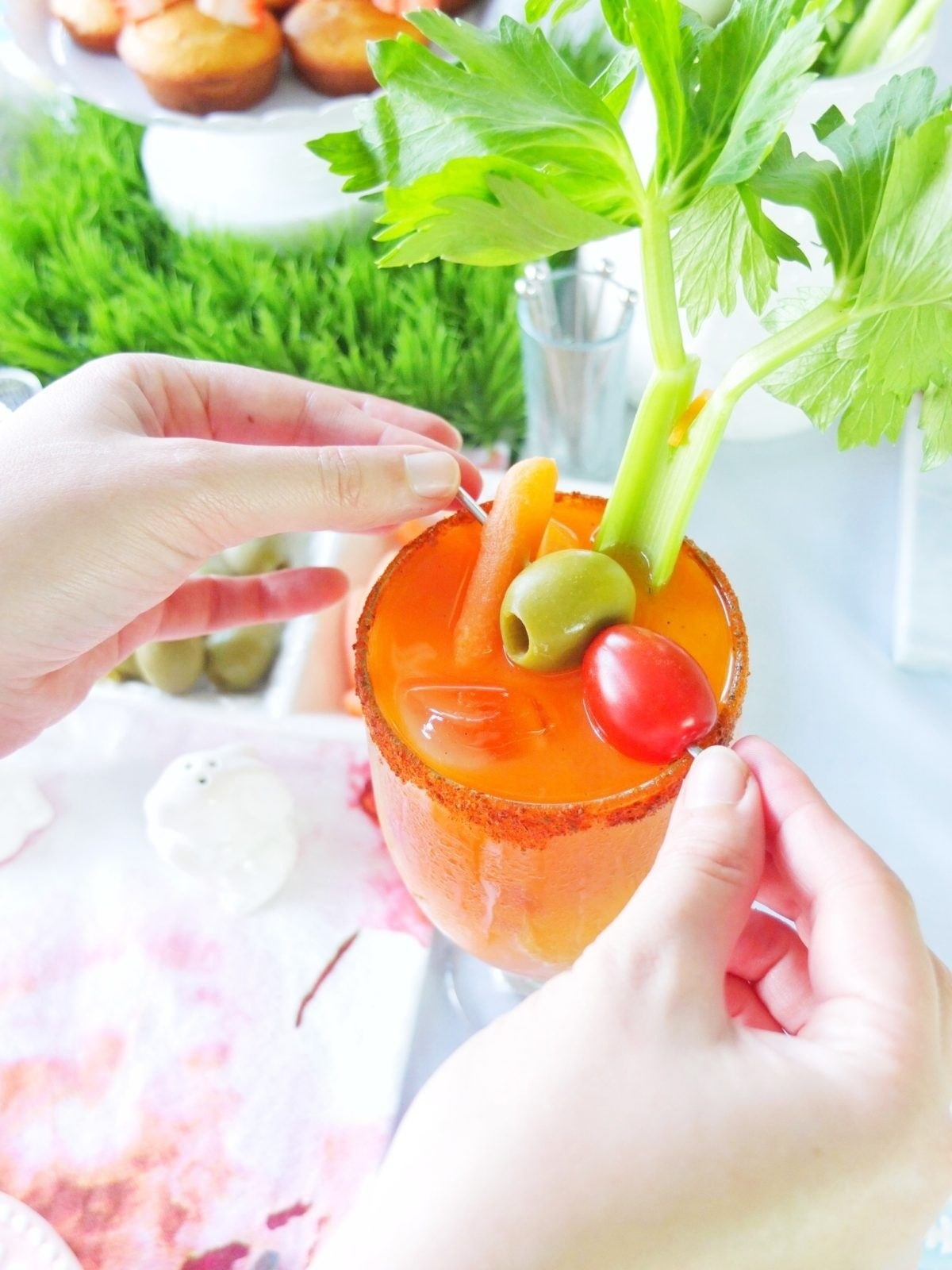 Putting tomato, olive, and pickled carrot garnish into a Bloody Mary.