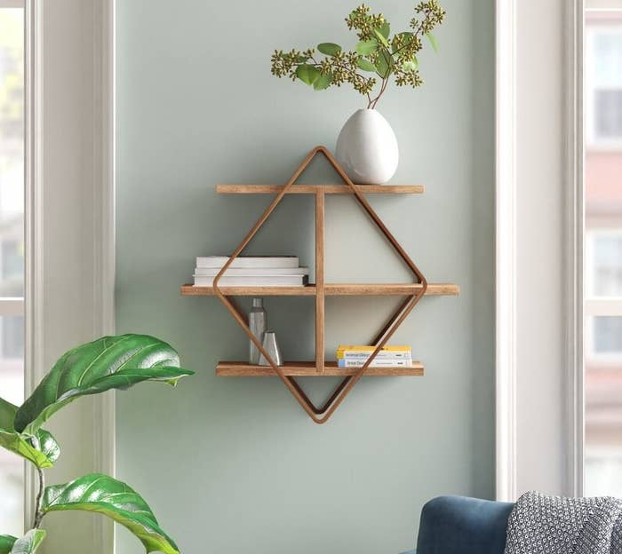 The shelf in rose gold with books and knick knacks on top