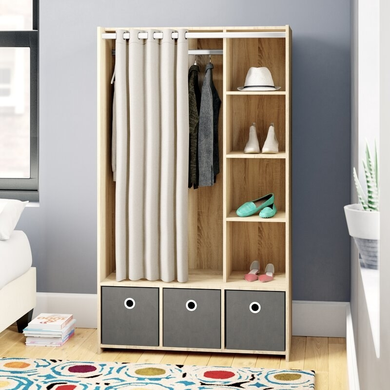 Armoire with three storage bins, four open shelves, and a hanging bar with fabric curtain