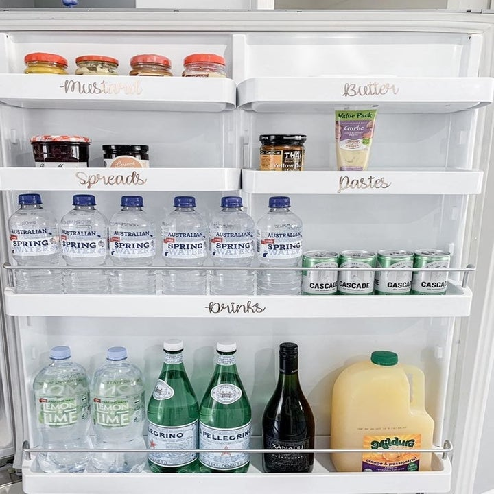 Various labels placed on shelves in a fridge door